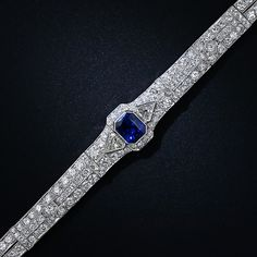 A stunning and exemplary 1930s vintage Art Deco bracelet, crafted in platinum and starring a radiant rich blue faceted emerald-cut sapphire weighing 5.09 carats. The enchanting royal-blue gemstone is flanked on each side by a shimmering kite-shape diamond leading to a pair of European-cut diamonds, followed, in turn, by a glistening row of French-cut diamonds which are repeated once more halfway down the bracelet.