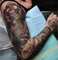 Grayscale sleeve tattoo about ravens. You can immediately spot the raven flying high and strong on the top of the arms. You can also see a bit of floral design as well as a few tribal themes too.