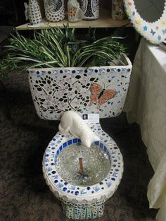 Ceramic toilet repurposed with mosaic tile & recreated into a fountain & planter.