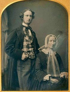 "Definitely the mid-1850s when plaid, checks and mixed  patterns where the height of fashion, but I rather think the mother of this very fashionabe young gent is thinking, ""Why, oh why, couldn't he get a plain blue serge?"""
