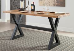 Glosco Counter Height Table  Cool counter height gives the Glosco sawbuck dining room table an elevated sense of style. Serving up a thick slab of solid mango wood, the plank-style table top is supported by a black tubular base for a fresh twist on modern-rustic design. Other items pictured in the image are sold separately.