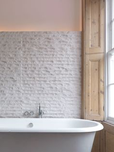 design bathroom with vintage inspired tub | love rough wall tiles + indirect light By McLaren.Excell
