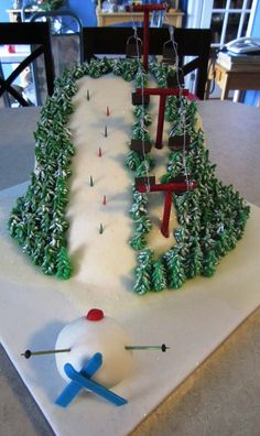 """An alpine ski race cake for my nephew who is a ski racer. Two 3"""" cakes - one chocolate, one vanilla - stacked, torted, and carved into a slope. I made ski race wickets with actual banners on them, but I made them well in advance of the cake in order for them to harden and didn't have the correct cake scale at that time. Turns out they were too big, so I had to go with coloured toothpicks instead. Of course, the joke is with the skier balled up in snow at the bottom of the race course."""