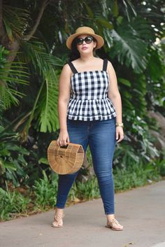 Girl With Curves blogger Tanesha Awasthi wears a gingham peplum, skinny jeans, boater hat, Tory Burch Miller sandals, Celine Audrey sunglasses and straw bag in Hawaii.
