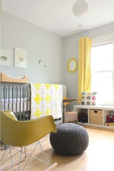 Light gray & yellow baby nursery with mid-century modern rocking chair, knitted pouf, chevron curtains, and globe pendant light