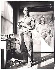 Willem de Kooning in front of an early version of Woman I in his studio at 85 Fourth Ave., New York City.