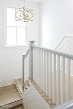 A staircase combines dove gray and natural wood floors with gold accents.