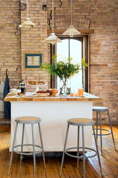 The owner of this Minneapolis farmhouse-style loft made a kitchen island from an old cabinet, which she topped with wooden packing crate slats. The stools are from Uline and the pendants are from The Foundry Home Goods.