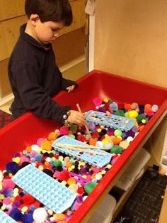 From Playfully Learning: Sensory Table idea-Pom Poms galore!