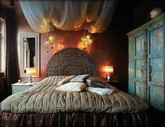 Bohemian bedroom. Has somewhat of a Moroccan, vintage, Indian....tantric vibe. Very pretty. I love the lanterns and ceiling drapes...and look at that gorgeous headboard.