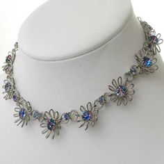 Sparkle with this unusual diamante necklace This Iris glass or rainbow diamante jewellery has silver flower links with striking blue pink green translucent stones