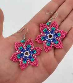 Pink, blue, and turquoise huichol flower seed bead earrings 🌸 Measurement of flower: L inches / W inches ***Please note that beaded jewelry is fragile, so please handle with love and care, thank you. Beaded Foot Jewelry, Beaded Jewelry Designs, Bead Jewellery, Beaded Flowers Patterns, Bead Embroidery Patterns, Beading Patterns, Brick Stitch Earrings, Seed Bead Earrings, Beaded Earrings