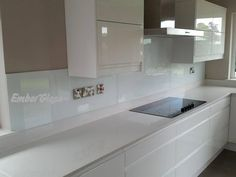 White glass splashback in modern white gloss kitchen. Ember Glass create bespoke glass products in any colour, pattern or image. Whether it's a splash back, worktop or table top, it's possible to personalise your glass to suit your existing decor, or taste. Visit www.glasssplashbacks.com for more inspiration!
