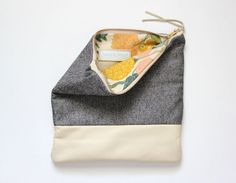 This foldover clutch is made from an elegantly soft wool in black and cream, blending together beautifully to give the look of grey fabric. Accented with