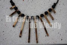 Llamativo collar simulando rayitos de sol, realizado a mano con alambre plano en tono oro viejo, y acompañado de abalorios de color negro en forma de perlita. Ideal para lucir con tu prenda favorita.