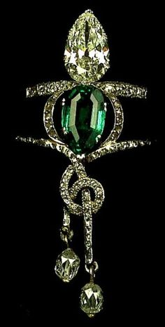 An Art Deco diamond, emerald and platinum ring, French, 1920s-1930s. Mounted in platinum and set with a pear-shaped diamond, a vari-cut emerald and numerous diamonds, with the shank terminating in a knot, suspending two faceted diamond drops.