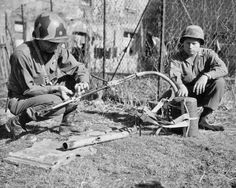 Members of the American 100th Infantry Division inspect a German flamethower or, flammenwerfer, in Butten, France
