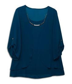 Plus size top features long sleeves with scoop neck styling. Chain pendant necklace accent. Layered look with roll tab sleeves. Chiffon fabric. Available in Burgundy, Teal, Black and Taupe. Available in junior plus size 1XL, 2XL, 3XL.