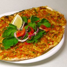 Lahmacun     A thin crisp, pizza-like dough topped with a spicy lamb mixture and eaten rolled up with a squeeze of lemon, a freshly baked lahmacun is one of the tastiest things you can eat.