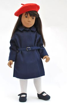 "15.5"" brunette Sasha doll (originally a dressed doll in Red Dress fashion) wearing the unisex Macintosh fashion, featuring navy coat with attached buckled belt and red felt beret, United Kingdom, 1982-86, by Trendon Toys. This outfit came without shoes, and curiously seems quite difficult to find natively in the United States and Canada."