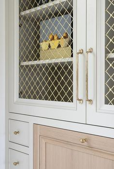 Light gray home office built in is fitted with flat front cabinets accented with brass knobs and a wood drop down desk top fixed below brass lattice front cabinets finished with brass pulls.