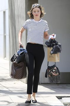 Miranda Kerr, 33 , looked chic in stripes as she juggled a bundle of bags in LA on April 22, 2016