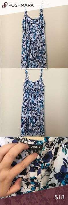 Torrid Size 2 blue and white floral sundress Very pretty and flattering. Has a tie under the bust. Comes to about the knee. There is a slight separation between the strap and the dress on one shoulder (shown in pic) but nothing that can't be stitched up real quick with a mending kit. Regardless, it's still together and wearable as is. Great condition, no stains or rips. Only worn twice. torrid Dresses Midi
