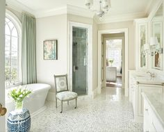Elegant bathroom features a gray chair on caster legs placed in front of a corner walk in steam shower clad in gray marble tiles and finished with a tilt out window. Micoley's picks for #luxuriousBathrooms www.Micoley.com