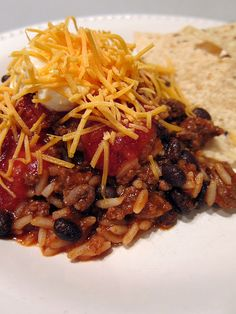 Taco Rice  1 lb. ground beef  1 packet taco seasoning  3/4 cup water  2 8 oz. cans tomato sauce  1 can black beans, drained  2 cups cooked white (I used Uncle Ben's Ready Rice)  tortilla or corn chips  your favorite taco toppings - salsa, cheese, sour cream, lettuce, tomatoes, etc