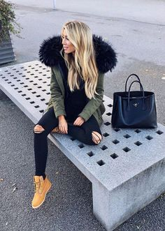 Janine Wiggert is casually chic in this understated winter style, consisting of a pair of distressed denim jeans, a furry green parka, and a pair of gorgeous classic timberlands. We love the simplicity of this look! Brands not specified.