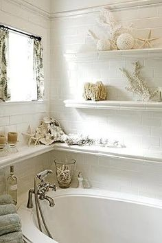 Shelves line walls around bathtub in bathroom with seaside beach cottage theme; shells, sponges, seashell home decor. Diy, repurpose, salvage, recycle, upcycle! For ideas and goods shop at Estate ReSale & ReDesign, Bonita Springs, FL