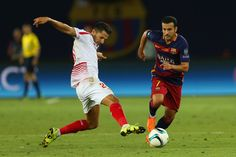 Pedro of Barcelona evades a tackle from Vitolo of Sevilla during the UEFA Super Cup between Barcelona and Sevilla FC at Dinamo Arena on August 11, 2015 in Tbilisi, Georgia.