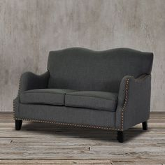 Add a classic touch and modern appeal to your living space with this contemporary loveaseat settee featuring stylish curves on the backrest and arms, bronze nail head trim details, birch frame, black legs with non-marking feet and dark gray elegant linen-polyester upholstery to offer a higher level of comfort and beauty to you, your family and your guests.