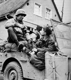The CO of the Military Police of 2nd US Armoured Division, Major Boochvon, talks with two very young Hitlerjugend members who were supposed to attack the advancing US forces. Kulmbach/Germany, April 15, 1945.
