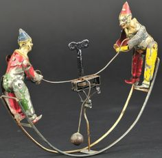 Germany, hand painted tin, features clown on either end of wire rocker base, key wind at center allows rocking and arm movements.