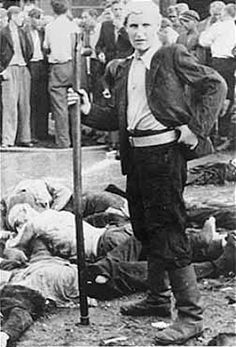 """Kaunas (Kovno) Lithuania, June 25-29, 1941: A Lithuanian named the """"Death Dealer"""" who took part in the torture and massacre of 68 Jews in the Lietukis garage of Kaunas poses for the camera still holding the iron pipe he used to bludgeon his victims to death."""