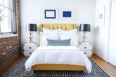 Loft bedroom features blue abstract art over a yellow tufted bed dressed in white and red rope shams and duvet and a blue lumbar pillow atop a black and white Greek key rug by Jonathan Adler flanked by white campaign chests topped with mercury glass lamps with black shades across from an exposed brick wall.