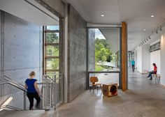 The pared-down interior of this educational facility in a Pittsburgh park features polished concrete floors, and tables and benches made of rough-cut wood.