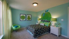Kids room with green apple decor and painting on wall.