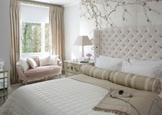"""In the master bedroom, von Stockhausen used silver to create a calm yet glamorous space. She chose a cherry blossom wallpaper with a silver leaf background to create a cool shimmer, while a soft pink loveseat, champagne satin drapes, and blush notes throughout round out the neutral scheme. """"A subtle layering of neutrals creates a comfortable and enveloping space,"""" says the designer. """"A few contrasts in the same hue create a gentle juxtaposition that's harmonious with the design."""""""