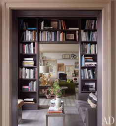 Bookshelves by Janson Goldstein in the #library frame a view of the #living room. The '40s Italian cocktail table was found at Mondo Cane, and the flooring is stained European oak.