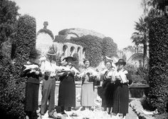 The Knotts and others at Mission San Juan Capistrano, California, circa 1940s. Walter and Cordelia Knott (second and third from the left) and others feed pigeons at Mission San Juan Capistrano. The bell wall and the ruins of the Old Stone Church can be seen in the background. From the Orange County Archives' Knott's Berry Farm Collection.