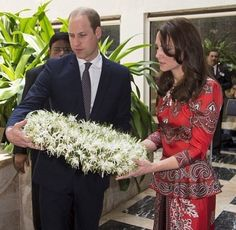 Kate & William Placing Wreath, at the Taj Palace Hotel Memorial, April 10, 2016.  Day 1, Royal Tour April, 2016. Princess Catherine is wearing a red Alexander McQueen suit / dress.