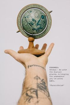 A photo of a man holding out his arm with a small wooden vintage world globe in his hand, with a wrist tattoo of Fernweh and a hand-drawn compass. Photo taken with Canon 650D Rebel T4i and 24-105mm lens, edited with VSCO Film 400+ in Adobe Lightroom. Perfect representation of travel or tattoos.