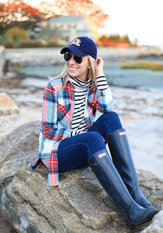 white and black striped shirt, plaid shirt, navy blue baseball cap, jeans, and black hunter boots