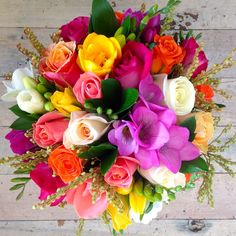 Handtied bouquet with a selection of beautiful blooms including White Chocolate (Cream) Roses, Miss Piggy (Blush coral) Roses, Frieda Roses, Hot Meringue (Soft yellow) Roses, Purple Cezzane  Roses, Assorted Freesias, Emerald Ruscus in soft and rich spring colour tones with accompanying foliage.