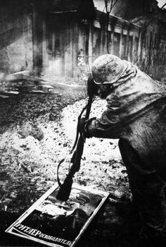 Red Army soldier smashes a German propaganda poster that reads Hitler the liberator.