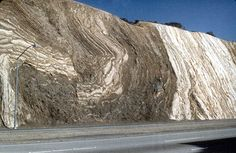 Photograph of severely deformed sedimentary rock layers exposed in a roadcut of the Antelope Valley Freeway (I-19) within the San Andreas fault zone near Palmdale, CA; view is about 330' wide