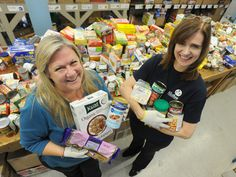 Kathleen Rose (left) and Norma Hergott, volunteers with the Waterloo Region Food Bank, show some healthier food options people might consider donating as the holidays approach.