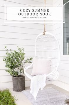 #ad A Cozy Summer Outdoor Nook with a beautiful white hanging chair, olive tree, small plants, candles, and outdoor rug. #SLPartner #SerenaAndLily @SerenaandLily | Summer patio decor. | Hanging chair under patio outside. | White outdoor decor for your white house. | White house exterior decor. | Olive tree in a basket. | Indoor outdoor rug under a white hanging swing. | Indoor Outdoor Rugs, Outdoor Living, Outdoor Decor, Small House Decorating, Decorating Tips, White Wicker Furniture, White Exterior Houses, Summer Diy, Summer Ideas